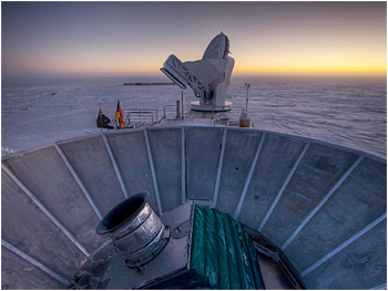 The sun sets behind BICEP2 (foreground) and the South Pole Telescope (background).  <i>Credit: Steffen Richter, Harvard University</i>