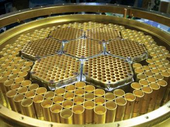 This honeycomb-like array of feedhorns at the 10-m South Pole Telescope directs radiation to superconducting detectors used to measure the polarization of the cosmic microwave background. The seven hexagonal cells in the center, about 5.8 cm across, are sensitive to radiation at frequencies of about 150 GHz. The larger feedhorns surrounding them are used for frequencies near 95 GHz. Progress in detector development is so rapid that within a year arrays should have sensitivities an order of magnitude greater than that of the state-of-the-art detector shown here. (Courtesy of the South Pole Telescope.)