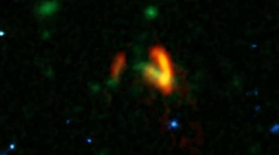 A composite image showing ALMA data (red) of the two galaxies of SPT0311-58. These galaxies are shown over a background from the Hubble Space Telescope (blue and green). The ALMA data show the two galaxies' dusty glow. The image of the galaxy on the right is distorted by gravitational lensing. The nearer foreground lensing galaxy is the green object between the two galaxies imaged by ALMA.   <i>Credit: ALMA (ESO/NAOJ/NRAO), Marrone, et al.; B. Saxton (NRAO/AUI/NSF); NASA/ESA Hubble</i>