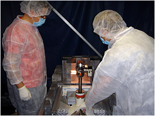 KICP physicist Juan Collar (left) and University of Washington graduate student Mike Marino inspect the CoGeNT experiment at the Soudan Mine in Minnesota. CoGeNT has detected a seasonal signal variation during its first year of operation. This is what scientists would expect if dark matter is made of Weakly Interacting Massive Particles (WIMPs), but the CoGeNT collaboration considers the results to be inconclusive.  <i>Image Credit: Courtesy of CoGeNT Collaboration</i>