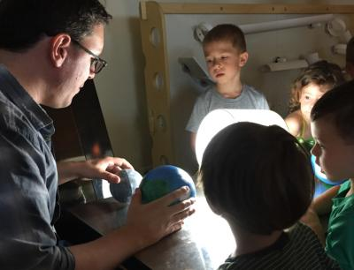 Jason Henning (left), a post-doctoral fellow at the Kavli Institute for Cosmological Physics at the University of Chicago, talks about eclipses with children Tuesday at the Bright Horizons at Lakeview, a Chicago pre-school on Lincoln Avenue. <i>Credit:</i> Neil Steinberg/Sun-Times
